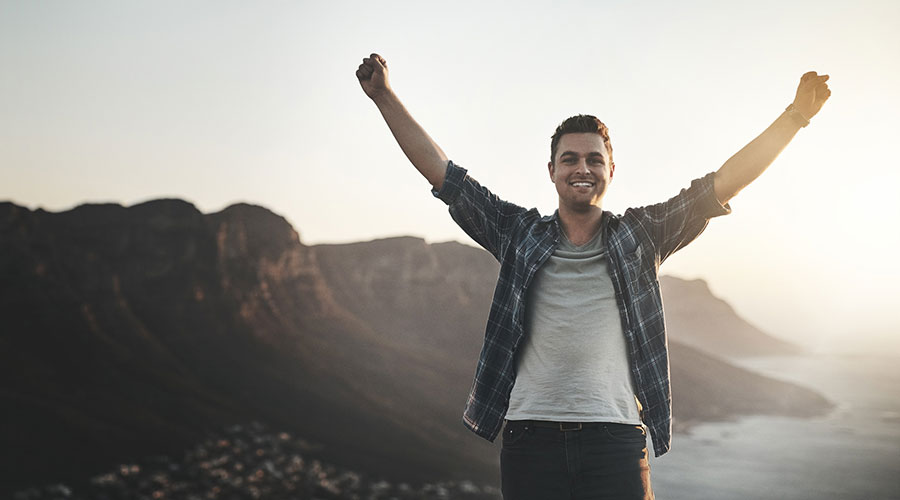 man on mountain top enjoying debt freedom